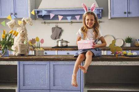 Ritratto della bambina felice che indossa le orecchie di coniglio sulla testa che riposa nella cucina accogliente con presente nelle mani. Copia spazio nella parte sinistra