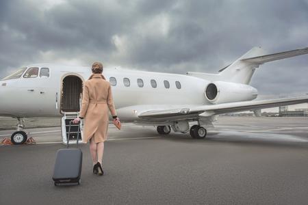 Volledige lengte vrouwelijke bagage houden tijdens het gaan naar prive-jet. Ze keerde terug naar de camera. Reis concept
