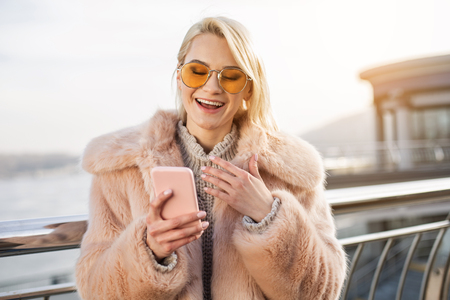 Funny message. Portrait of cheerful girl in sunglasses is standing on street and holding pink mobile phone. She is looking at screen of gadget with wide smile