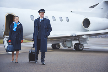 Full length portrait of cheerful stewardess and glad standing near aircraft. Profession concept Stock Photo