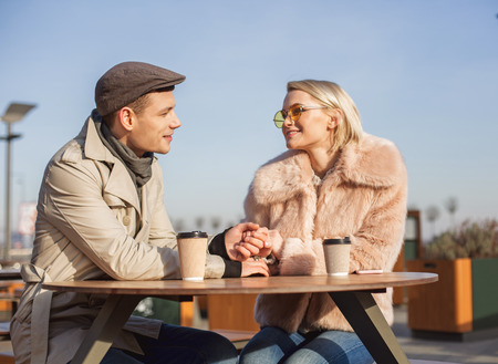 In love. Attractive positive happy girl in sunglasses is looking at her stylish boyfriend and smiling while having coffee with him. They are holding hands tenderly