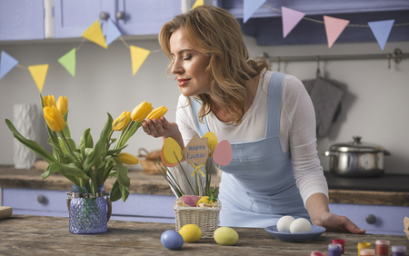 Perfect aroma. Satisfied woman sniffing beautiful tulips while preparing for easter holiday at home