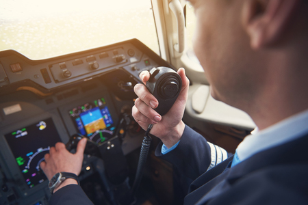 Close up pilot hand taking by portable radio set in cabin while navigating plane. Occupation and communication concept Stockfoto