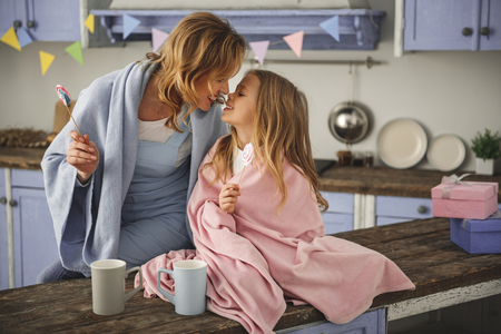 Glad mother and child relaxing with sweets in hands wrapped in blanket. They contacting with their noses. Copy space in right side