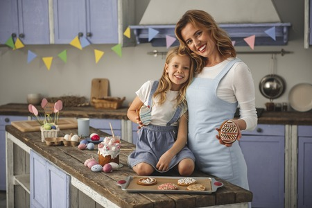 Portrait of enjoyed mother and daughter standing in the cuisine and holding cookies in the shape of eggs. Copy space in left side Reklamní fotografie - 96373218