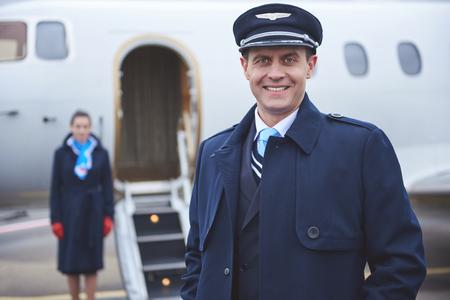 反対側の平面に位置しながらカメラを見ているビーミングパイロットの肖像画。労働概念 写真素材