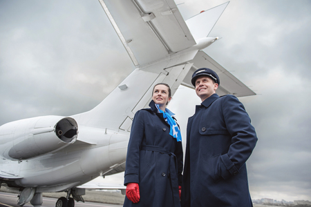 Low angle portrait of cheerful air-hostess and glad pilot locating near airplane outdoor. Profession concept