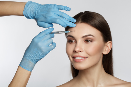 Portrait of cheerful girl getting surgical facial correction. Beautician arm injecting liquid into her forehead. Isolated