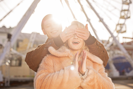 Can you guess who. Excited happy girl is resting outdoors with her boyfriend who is standing behind her. He is covering her eyes by hands and smiling. Ferris wheel and sunshine on background Banco de Imagens - 96373276