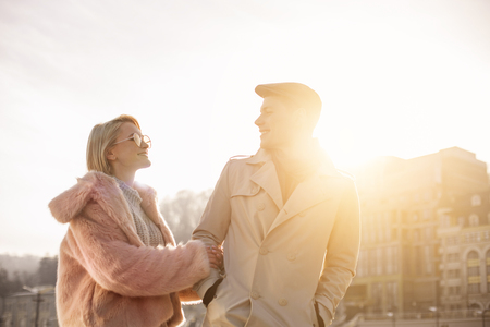Look at me. Cheerful young romantic girlfriend and boyfriend are standing on street in sunlight. They are looking at each other with love Stok Fotoğraf