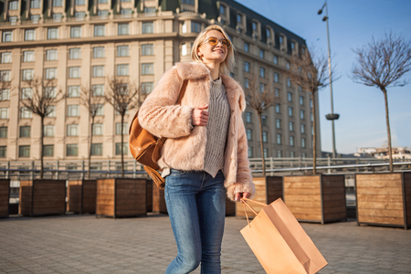 Full of joy. Cheerful young stylish woman in sunglasses is holding package and expressing delight while going along street. She is wearing fur coat