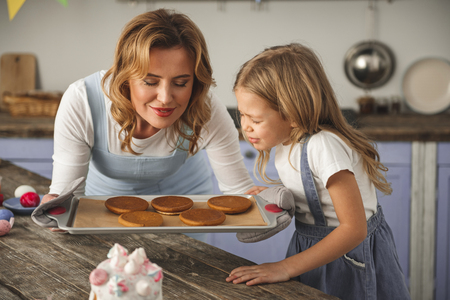 Delighted mother and child standing in the kitchen and sniffing cookies with eyes closed