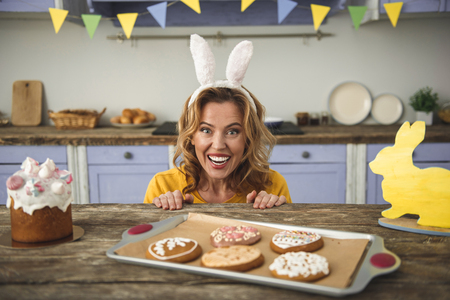 Portrait of cheerful lady in funny bunny headband sitting at kitchen table with easter cake, cookies and yellow rabbit statuette. She is looking at camera and laughing