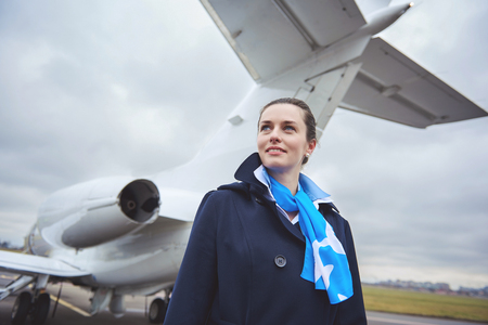 Portrait of stewardess expressing happiness while standing near aircraft on street. Occupation concept