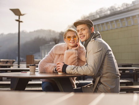 Nice time together. Portrait of cheerful relaxed smiling couple is sitting at table and drinking coffee while resting outdoors. They are looking at camera with joy Stock Photo