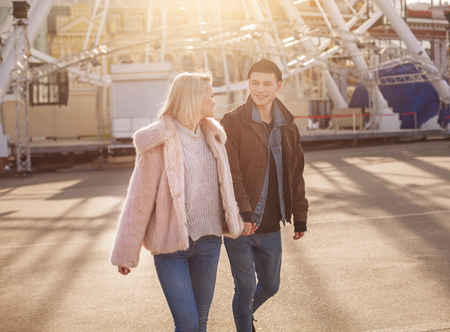 Lovely weekend. Happy young girlfriend and boyfriend are walking on square while holding hands and looking at each other with love Stock Photo