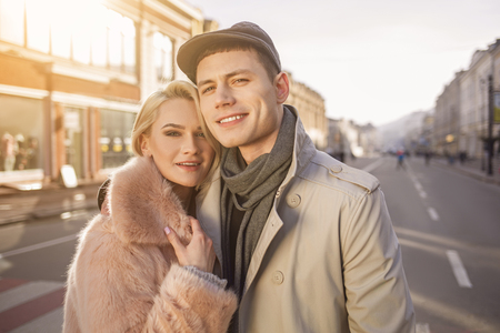 Happy spring day. Portrait of young delighted guy and attractive girl are standing together on street. They are looking at camera with smile while hugging and having rendezvous Stock Photo