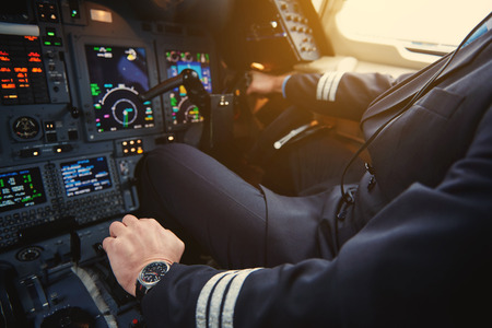Close up aviator hand working with aircraft appliance in cockpit. Appliance and job concept