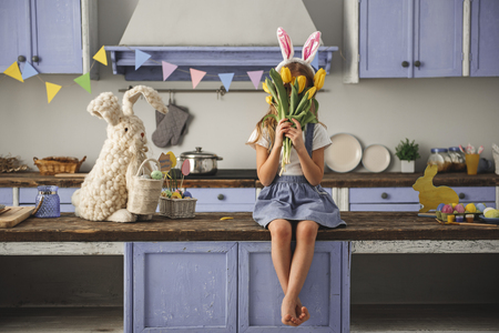 Child reposing in the cooking room decorated for easter. She is hiding her face with flowers. Copy space in right side