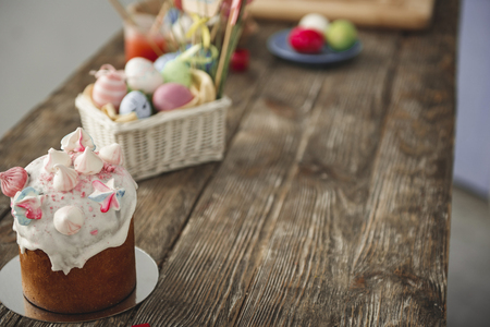 Close up of sweet bread and box with colored eggs on the timbered desk. Focus on bakery. Copy space in right side Reklamní fotografie