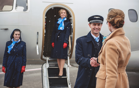 Cheerful aviator shaking hands young businesswoman near plane. Happy stewardesses watching at them. Occupation concept