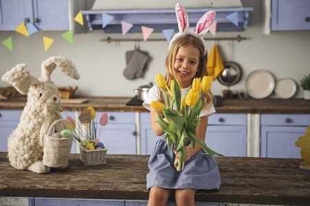 Portrait of pleased girl celebrating easter at home. She is extending hand with bunch of yellow tulips