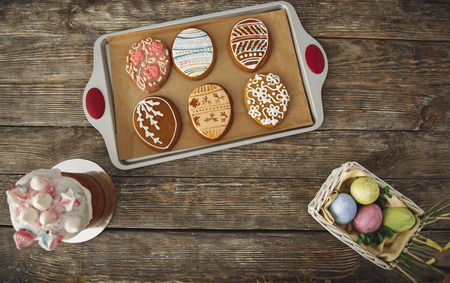Following traditions. Top view of egg shaped cookies decorated with colorful patterns of glaze, easter cake with quaint topping and small straw basket filled with painted eggs Stock Photo