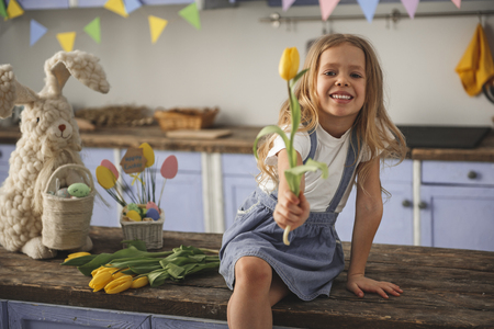 Portrait of cheerful girl congratulating with easter. She is extending hand with one spring flower while resting indoors. Copy space in left side