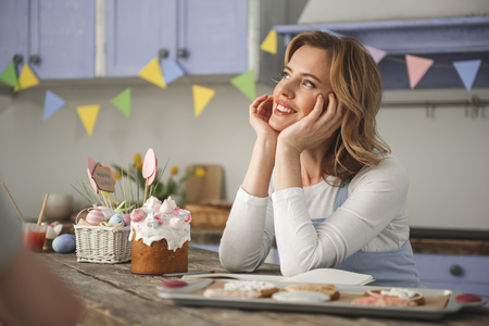 Delighted young woman with pensive expression reposing in the kitchen. Traditional easter food standing nearby