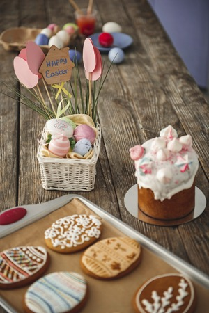Cookies on a tray, painted eggs and sweet bread standing on wooden surface