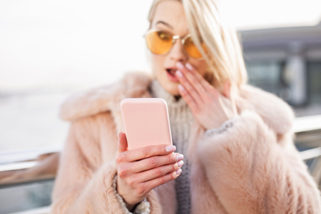 Shocking news. Close up of pink smartphone in hand of surprised girl. She is looking at screen of gadget with eyes wide open while standing on street. Selective focus