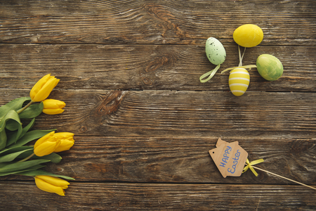 Top view of yellow tulips and faberge eggs lying on the wooden table Фото со стока - 96373681
