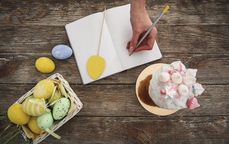 Top view of female hand writing in notebook, straw basket with pained eggs and easter cake with interesting topping are standing on wooden table Stock Photo