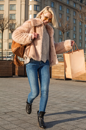It is nice day. Full length of charming blissful young woman is holding package and expressing gladness while going along street
