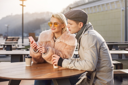 Look here. Involved young boyfriend and girlfriend are sitting at table in open air restaurant and drinking hot coffee while using modern smartphone. They are looking at screen of gadget with interest