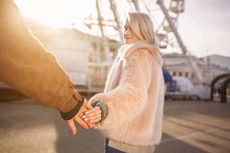 私を行かせないでください。若いロマンチックなガールフレンドとボーイフレンドの手のクローズアップ選択的な焦点。日没の光の中で通りに立っ