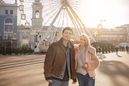 Best couple. Portrait of delighted young girlfriend and boyfriend are posing on square against ferris wheel. They are looking at camera with smile. Sunset on background