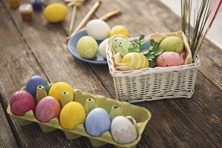 Close up of colored easter eggs lying in different boxes on the wooden table