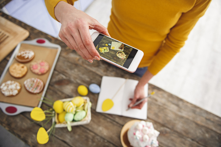 Top view of woman in kitchen making photo of her hand writing in notebook. Basket with pained eggs, cookies and glazed easter cake are standing on table. Focus on cellphone Stock Photo