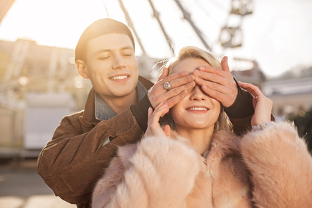 Surprise. Cheerful girl is trying to guess who is standing behind her. Her boyfriend is covering her eyes by hands and smiling while enjoying their rendezvous. Ferris wheel and sunshine on background