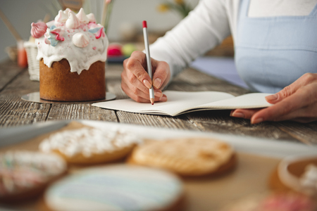 Close up of female hand making notes with pencil in copybook. Easter bread is on the table Stock Photo