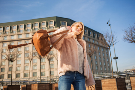 Low angle of delighted gorgeous girl is standing on street and holding her bag. She is looking aside with smile while enjoying warm spring day