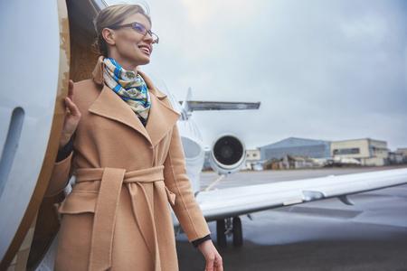私用飛行機から行く女性に微笑む低角度。旅行コンセプト