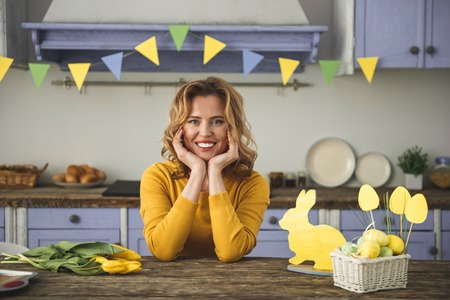 Favorite holiday. Waist up portrait of contented female sitting in country style kitchen, she is holding her head on hands and smiling. Easter eggs and flowers are on table. Colorful flags on background
