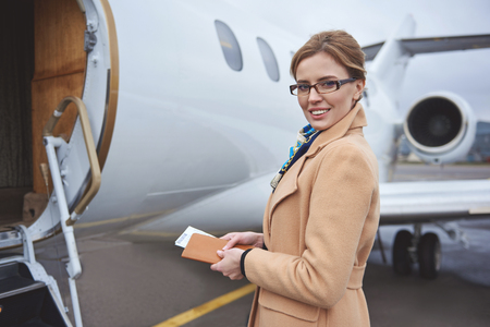 Portrait of cheerful businesswoman keeping tickets while standing near plane on street. Career concept