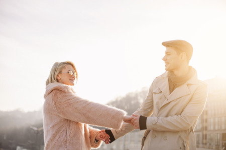 In his strong arms. Charming young woman is standing on square in sunlight while holding hands with happy delighted boyfriend. They are looking at each other with admiration and love Stok Fotoğraf