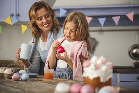 Happy mother and daughter standing close indoors. Mom is holding cup and looking her kid colorizing holiday eggs. Focus on females. Copy space in right side Stock Photo