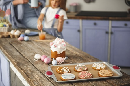 Traditional easter bakery standing on the dining table. Mom and daughter standing on background Imagens