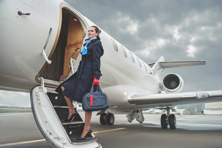 Full length portrait of cheerful young air-hostess entering airplane while holding baggage. Job concept