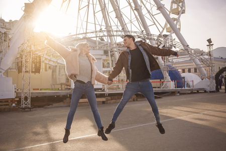 My only one. Full length of delightful romantic couple is jumping on street while holding hands. They are looking at each other with joy. Sunset light and ferris wheel on background